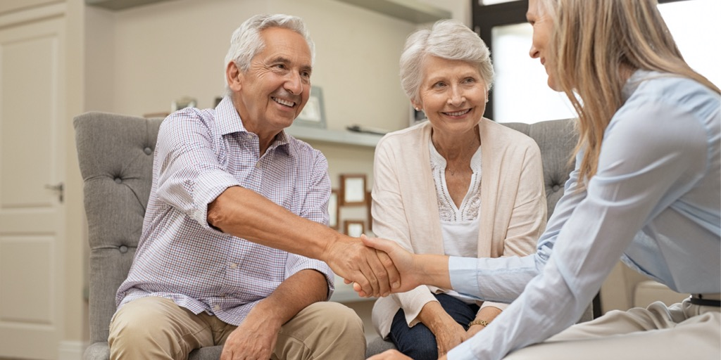 senior-couple-shaking-hands-with-financial-advisor-picture-id1029343906